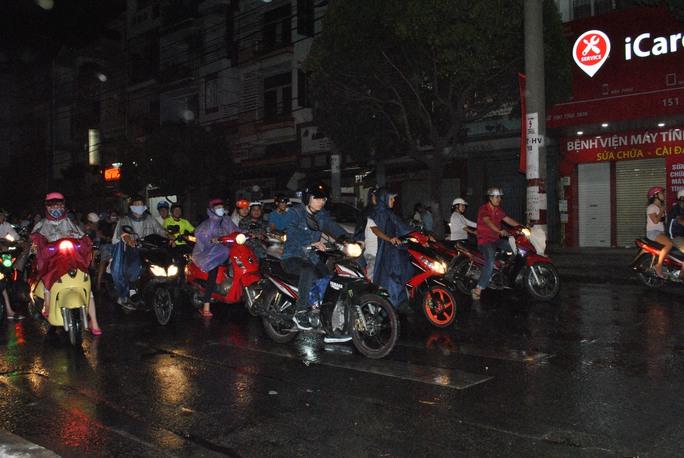 Người dân mặc áo mưa lưu thông trên đường Hùng Vương (quận 5, TP HCM)