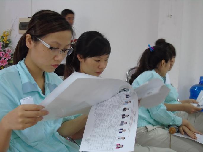 Những công nhân của Công ty Canon đọc thông tin ứng viên đại biểu Quốc hội và HĐND các cấp nhiệm kỳ 2016-2021