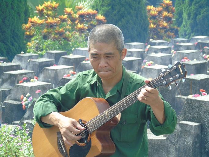 Nhạc sĩ Trương Quý Hải, cựu binh Sư đoàn 356, ôm đàn ghi ta và hát bài Về đây đồng đội ơi tại Nghĩa trang liệt sĩ Vị Xuyên để tưởng nhớ về những đồng đội của mình hy sinh tại mặt trận Vị Xuyên nhưng chưa tìm được hài cốt - Ảnh: Văn Duẩn
