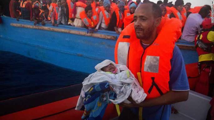 Một người đàn ông chạy khỏi Libya bế đứa con 5 ngày tuổi sau khi được giải cứu hôm 29-8 Ảnh: AP