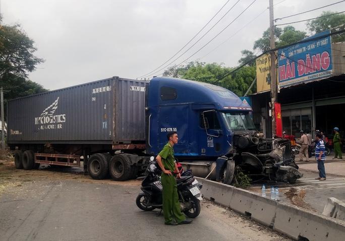 Chiếc xe container nằm chắn ngang cả làn ô tô và xe 2 bánh ở hướng ngược lại, đầu xe bị hư hỏng nặng