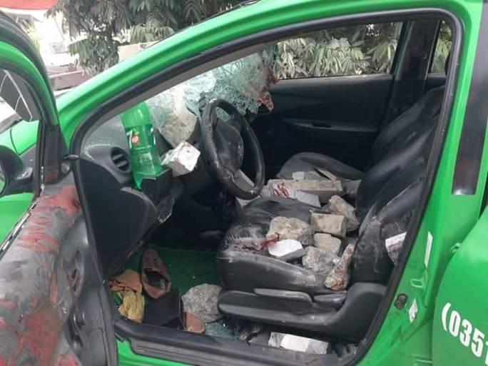 Gạch đá mà người dân ném vào xe taxi chở 2 thanh niên tới địa phương chém người