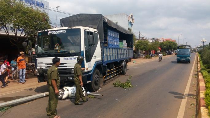 Chiếc xe tải chở bia cuốn một chiếc xe máy cùng trụ đèn xuống gầm
