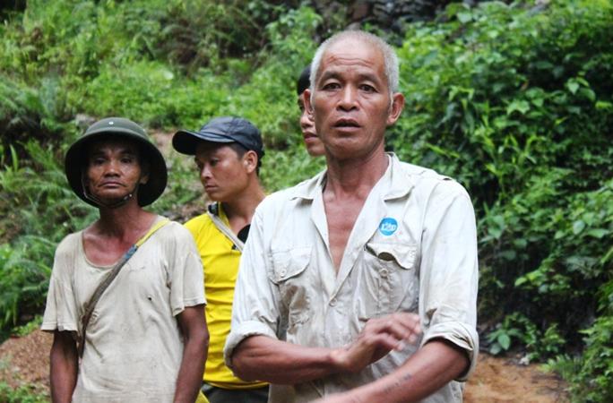 Ông Bùi Văn Quyên (bìa phải) và người thân đang chờ các cơ quan chức năng đưa thi thể anh Huyền lên để về lo hậu sự