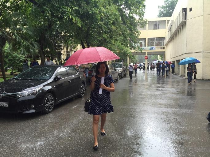 Thí sinh đội mưa đến trường thi