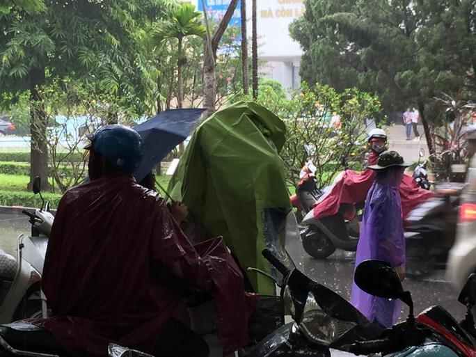 Phụ huynh trùm áo mưa chờ con làm thủ tục dự thi