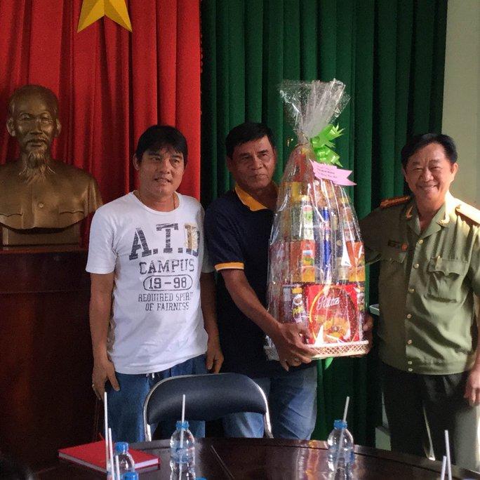 Giám đốc Công an tỉnh Bình Dương (bìa phải) trao quà cho đại diện Đội Phòng chống tội phạm Phú Hòa