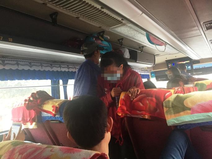Một hành khách phải len lỏi trước dòng người đang ngồi dưới sàn để tìm vị trí trống để ngồi.