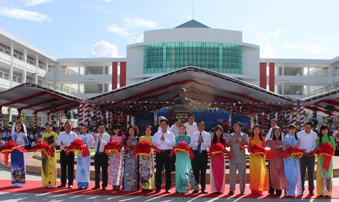 Các đại biểu đang thực hiện nghi thức cắt băng khánh thành vào sáng 3-9 tại Trường PTTH Võ Văn Kiệt.