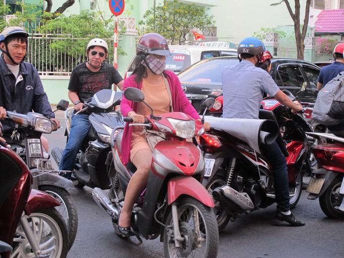 Người đi xe máy len lỏi qua đám đông tại ngã tư Hồ Xuân Hương-Bà Huyện Thanh Quan (quận 3)