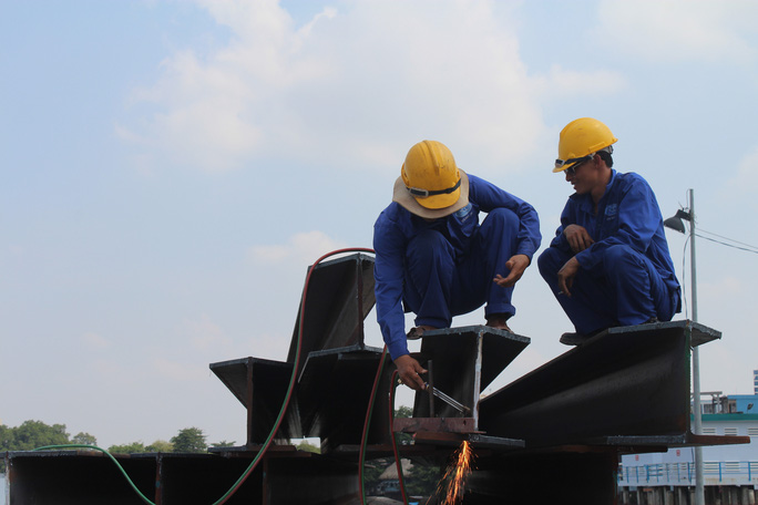 Công nhân hàn lắp các dầm trên công trường cầu Ghềnh, hai dầm cầu và nhiều nguyên vật liệu được mượn khu vực dự án lấp sông để tập kết