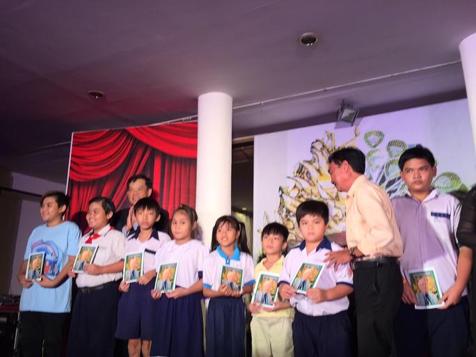 Nhạc sĩ Trương Minh Châu đại diện gia đình cố soạn giả Viễn Châu trao 5 phần học bổng của gia đình cho các em học sinh con nghệ sĩ nghèo.
