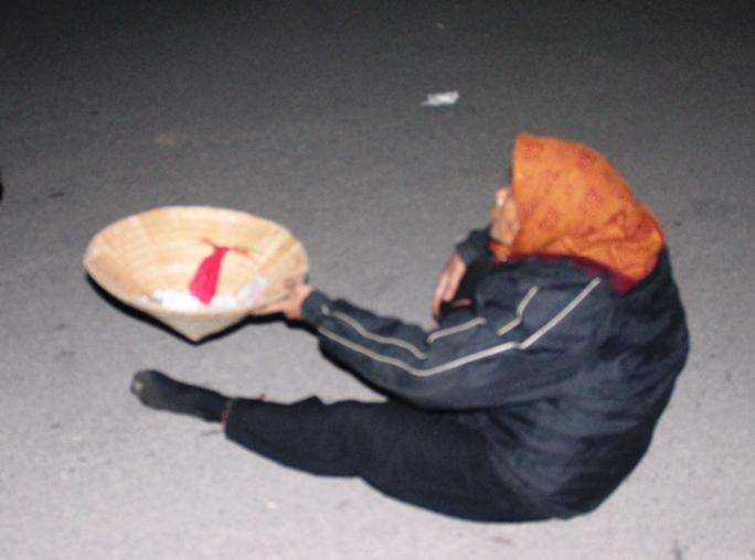 Một bà cụ ngồi dưới lòng đường ngửa nón xin tiền du khách