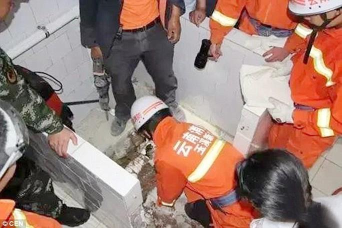 Các lính cứu hỏa nỗ lực giải cứu bé gái sơ sinh kẹt trong bồn cầu. Ảnh: CEN