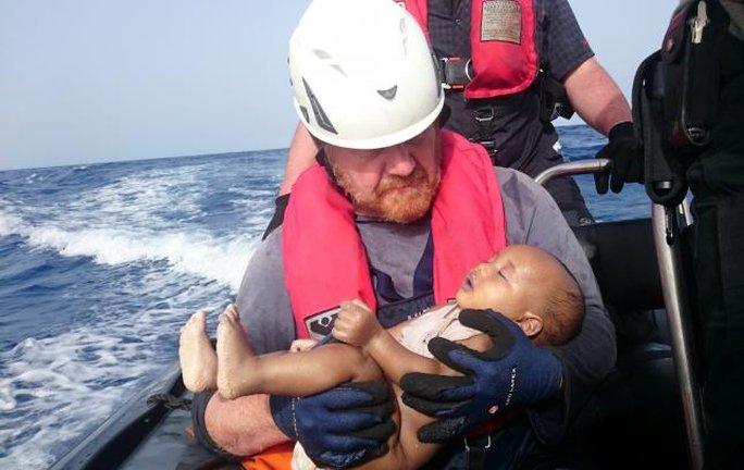 Trong vòng tay nhân viên cứu hộ của Sea-Watch, đứa bé vẫn như đang ngủ bình yên. Ảnh: Reuters