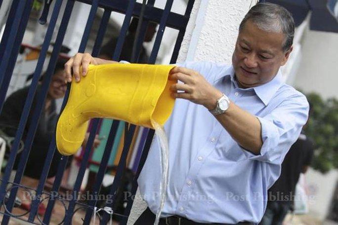 Ông MR Sukhumbhand Paribatra trút nước khỏi ủng cao su. Ảnh: Bangkok Post