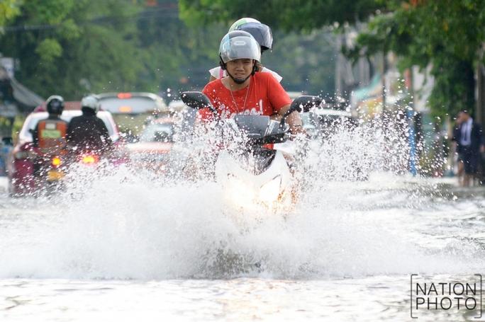 Người dân chạy trên đường phố ngập nước ở quận Chatuchak hôm 20-6. Ảnh: Nation