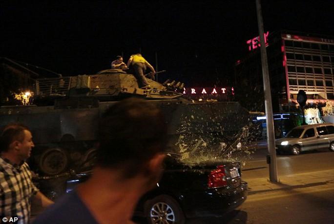 Một xe tăng quân đội ở trung tâm Ankara trườn lên ô tô khi người biểu tình cố ngăn nó di chuyển. Ảnh: AP