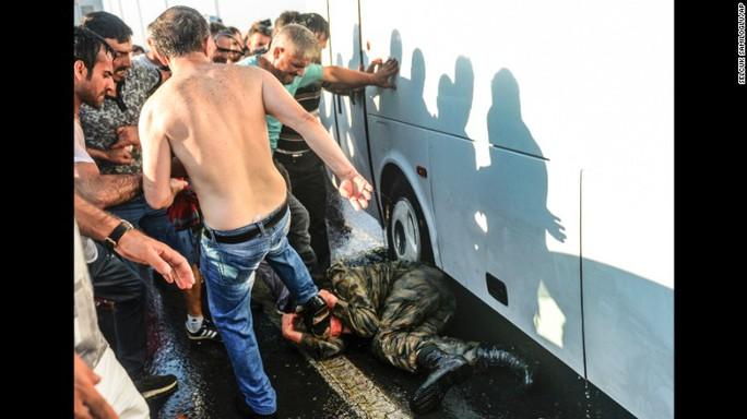 Binh lính đảo chính bị đánh trên cầu Bosporus hôm 16-7. Ảnh: AP