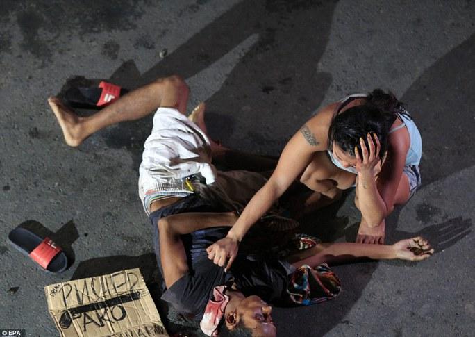 Một người vợ than khóc bên xác chồng ở TP Pasay, phía Nam Manila. Ảnh: EPA