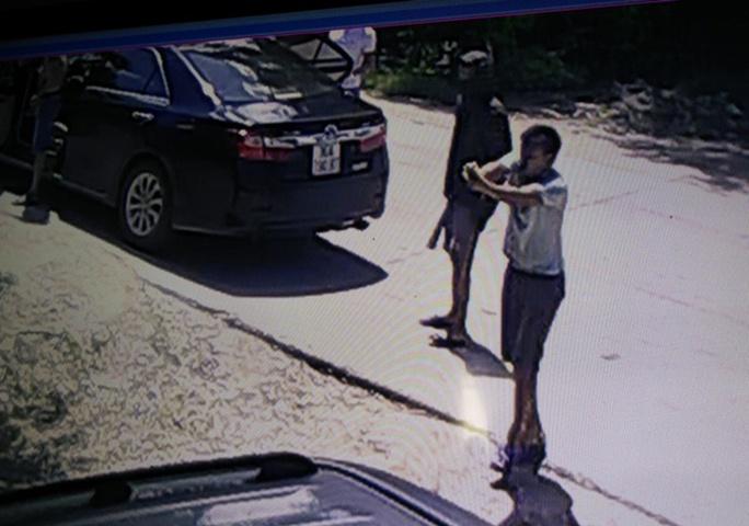 Một người từ trên ô tô bước xuống cầm súng ngắn bắn nhiều phát về phía gia đình ông Trịnh Ngọc Đỉnh - Ảnh cắt từ camera