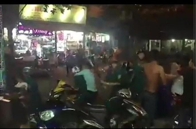 Một thanh niên đang kẹp cổ khống chế một người đội nón bảo hiểm, mặc áo dân quân (ảnh từ clip)