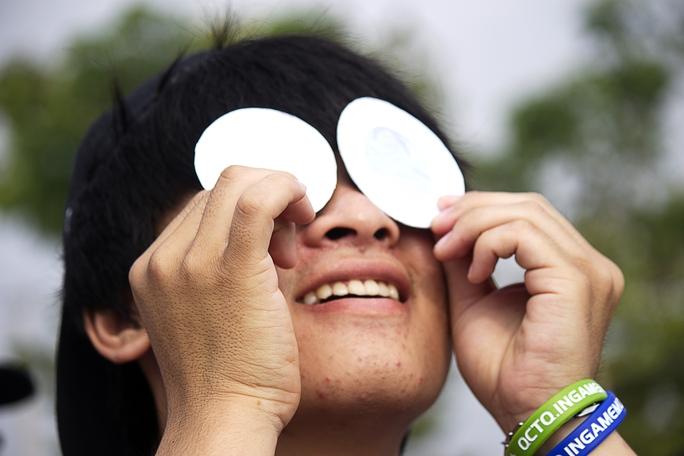 Một bạn trẻ hào hứng quan sát Nhật thực bằng tấm lọc ánh sáng để đảm bảo an toàn cho mắt.
