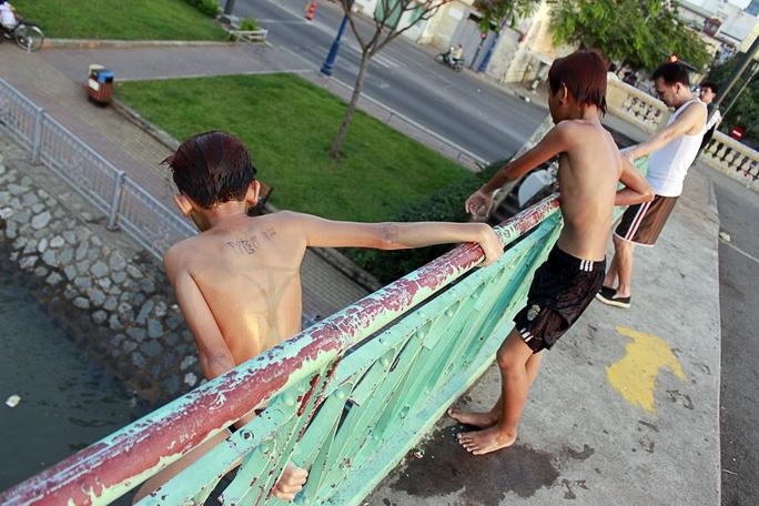 Tuy nhiên, nhiều trẻ em vẫn thường xuyên tụ tập tại các cây cầu này để nhảy sông và bơi lội. Trong ảnh: Hai cậu bé leo qua rào chắn chuẩn bị nhảy xuống kênh Bến Nghé.