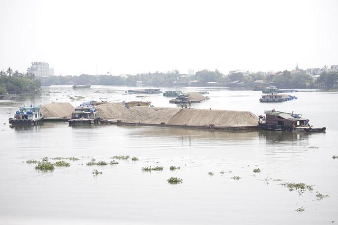 Chiều 21 - 3, nước sông Sài Gòn dâng cao, lực lượng chức năng liên tục tuần tra, các sà lan chở cát không thể lưu thông qua cầu Bình Lợi cũ đành đi đường khác hoặc neo đậu hai bên bờ sông đoạn cầu Bình Triệu.
