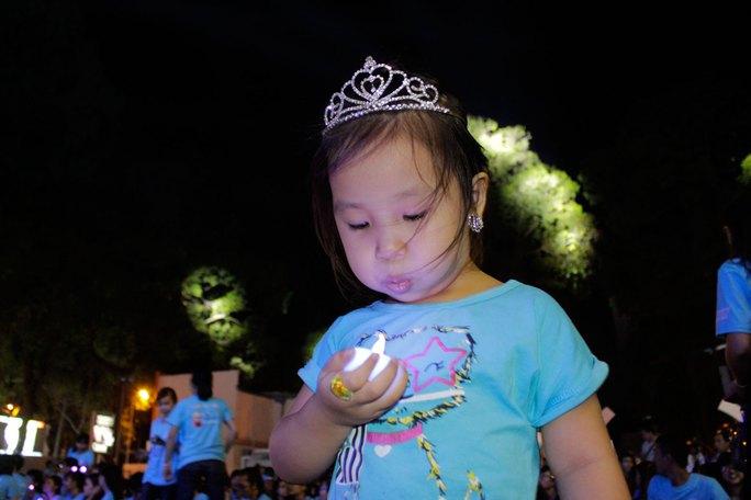Một tình nguyện viên nhí dễ thương thử thổi cây nến đèn led.