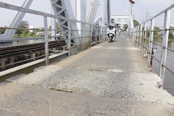 Phần giữa cây cầu là những tấm xi măng đặt liền nhau đã nứt nẻ và mục lổm chổm nhiều chỗ.