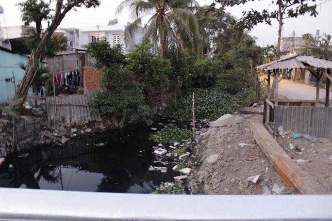 Mặc dù nâng đường để chống ngập nhưng con kênh thoát nước cạnh đoạn đường này lại chìm trong rác và lục bình, không hề được dọn dẹp nạo vét thông thoáng.
