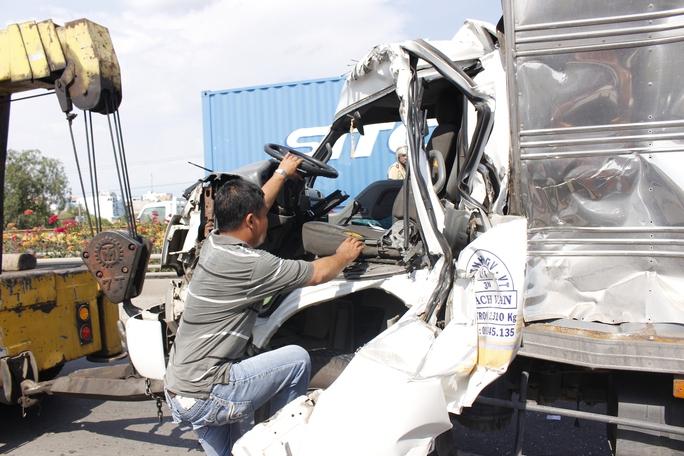 Đầu xe tải bị bẹp dí, tài xế xe lồm cồm bò ra từ ca-bin.