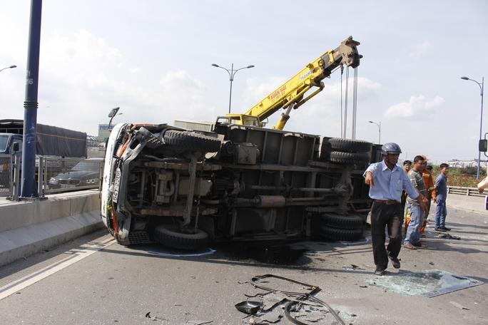 Xe tải mang gây tai nạn nằm lật chắn ngang trên cầu.