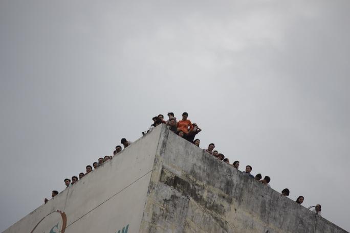 Mặc dù bị cấm nhưng nhiều người vẫn leo lên tầng thượng của tòa nhà cao tầng mong được nhìn thấy đoàn xe hộ tống tổng thống.