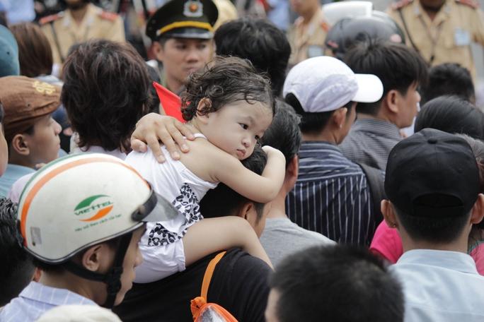 Một em bé mệt mỏi vì phải chờ đợi quá lâu, chen chúc giữa đoàn người đông đúc.