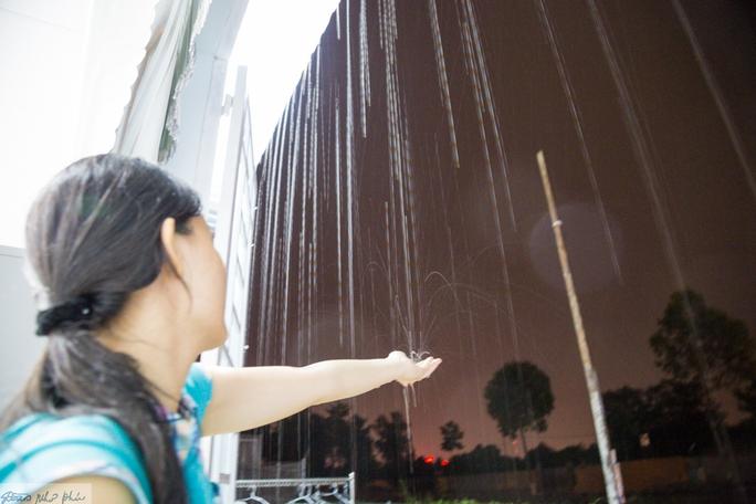 Một người dân ở phường Phú Thọ, TP Thủ Dầu Một thích thú hứng những giọt mưa vàng
