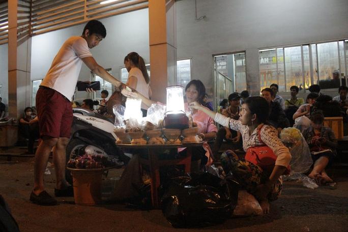 Nhiều người mua tạm ít đồ ăn nhẹ lót bụng trong khi chờ đợi mua được vé để về quê.