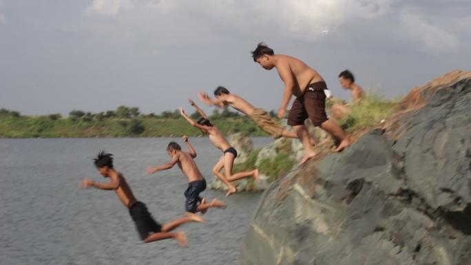 Thấy bên trên có một số người đứng quan sát và hò reo, nhiều em nhỏ hào hứng biểu diễn những cú nhảy trên không trước khi tiếp nước để chứng tỏ tài bơi lội của mình.