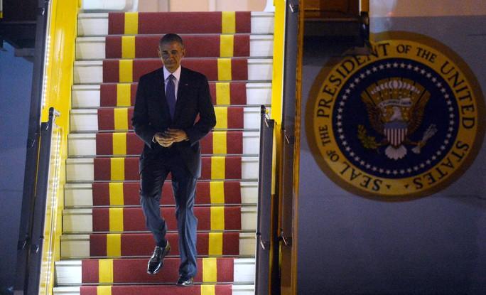 Tổng thống Mỹ Barack Obama tươi cười bước xuống cầu thang chuyên cơ Không lực Một tại sân bay Nội Bài. Ảnh: Reuters