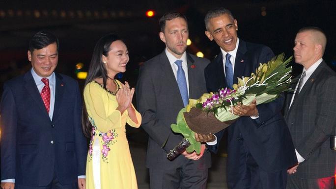Tổng thống Mỹ Barack Obama được tặng hoa ngay khi đặt chân xuống sân bay Nội Bài. Ảnh: AP