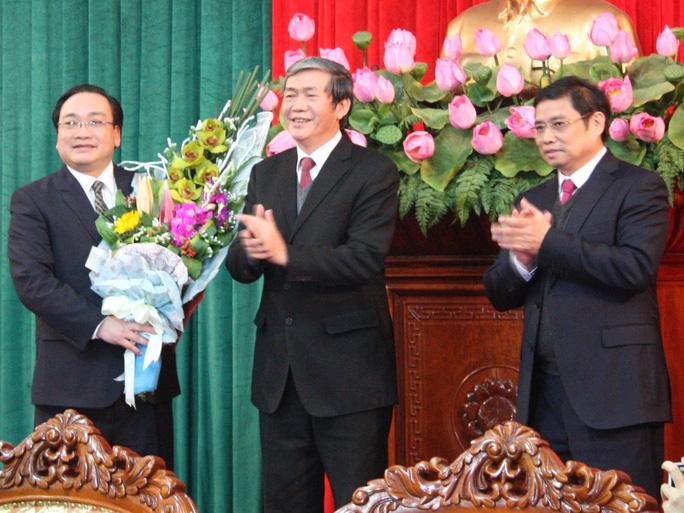 Ông Đinh Thế Huynh (giữa) thay mặt Bộ Chính trị trao quyết định phân công nhiệm vụ làm Bí thư Thành ủy Hà Nội cho ông Hoàng Trung Hải (trái). Trưởng ban Tổ chức Trung ương Phạm Minh Chính (phải) cùng tham dự sự kiện