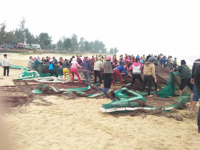 Người dân tập trung cứu hộ tàu cá mắc cạn.