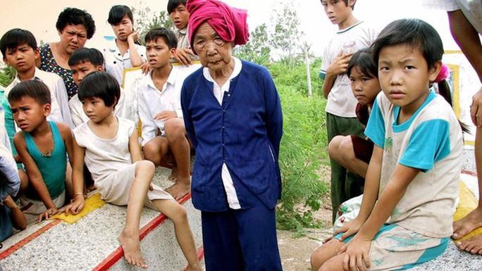 Bà Bùi Thị Nhi, 73 tuổi (giữa) tại mộ của cha mẹ và 3 người cháu gái của bà đã thiệt mạng trong cuộc thảm sát ở Thạnh phong, Bến Tre, năm 1969. Ảnh: Tư liệu