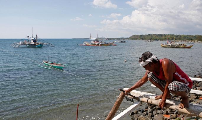 Ngư dân Philippines sửa chữa tàu đánh cá gần bãi cạn ScarboroughẢnh: REUTERS
