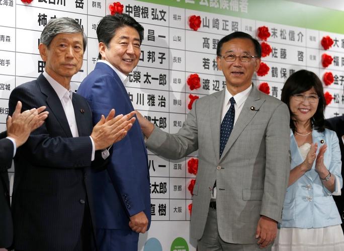 Thủ tướng Shinzo Abe cài hoa vào tên ứng viên được kỳ vọng giành được ghế ở Thượng viện tại trụ sở LDP  Ảnh: REUTERS