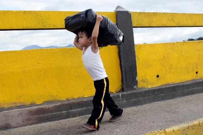 Một bé trai Venezuela mang gói hàng mua được tại Colombia hôm 10-7 Ảnh: Reuters