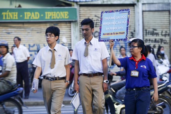 Tình nguyện viên dẫn thí sinh tới điểm thi Trường ĐH Khoa học Xã hội và Nhân văn TP HCM. Ảnh: Hoàng Triều