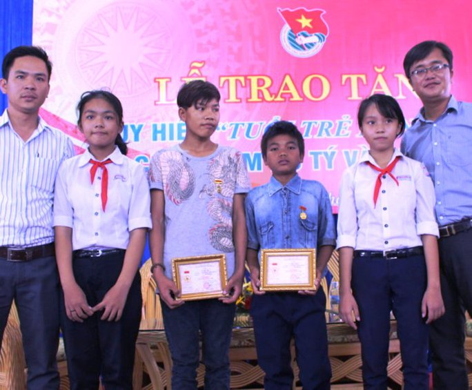 """Hai cậu bé chăn bò Bo Tý và Cao Lâm nhận huy hiệu """"Tuổi trẻ dũng cảm"""" chụp ảnh cùng 2 trong 5 nữ sinh được cứu sống"""
