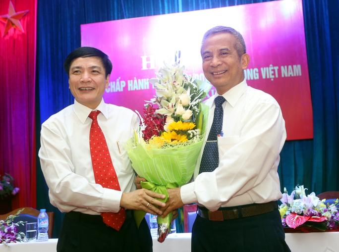 Ông Bùi Văn Cường (trái) nhận hoa chúc mừng từ ông Đặng Ngọc Tùng, nguyên Chủ tịch Tổng LĐLĐ Việt Nam Ảnh: Văn Duẩn